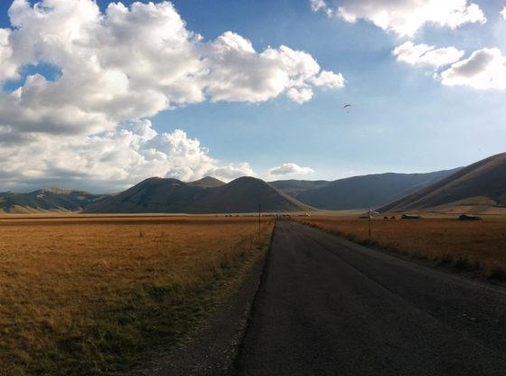 La foto mostra una strada in primo piano e colline sullo sfondo