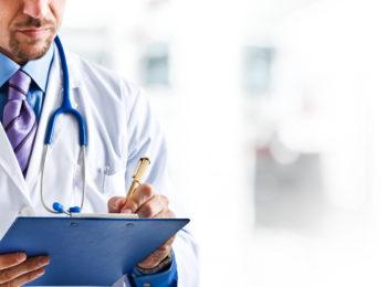La foto mostra un medico che scrive su una cartella clinica