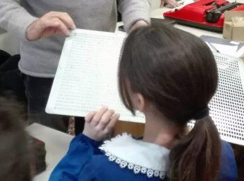 La foto mostra una bambina della quinta elementare che tocca un libro tattile