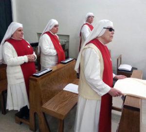 La foto raffigura suore non vedenti in preghiera mediante ausili Braille e Braillenote