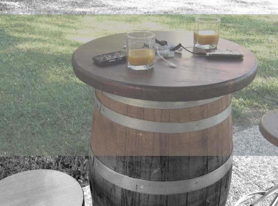 L'immagine mostra un tavolo a forma di botte con cellulari e bicchieri