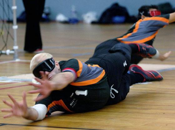 La foto ritrae un atleta non vedente che pratica il torball