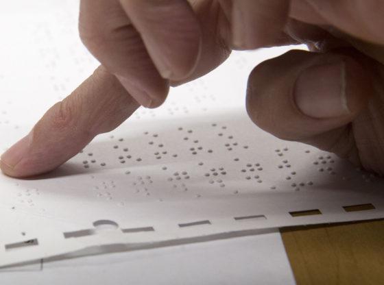 La foto mostra un dito che scorre un foglio scritto in Braille